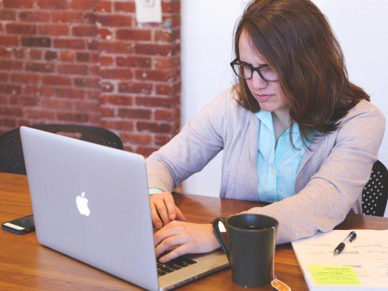 wanita berjas duduk menghadapi laptop.faktor stres kerja
