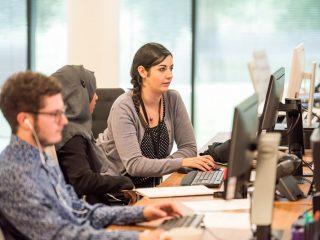 3 orang pekerja atau karyaean satu wanita berkacamata satu berhijab dan seorang lelaki di tempat kerja yang mengalami burnout pekerjaan