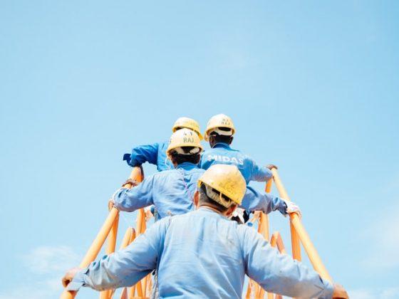 Pekerja berbaju biru dengan topi kuning menaiki tangga ke langit biru
