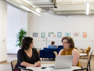 Dua karyawan perempuan berbicara seputar konsultasi psikologi karyawan