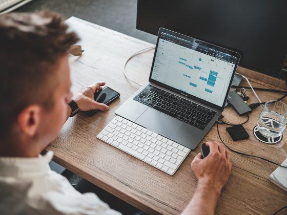 Seorang pria tengah mengatur perencanaan manajemen stres kerja di laptop