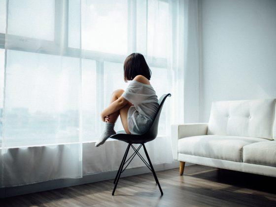 wanita duduk menghadap jendela.cara mengatasi panik corona